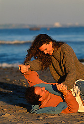 Couple wrestling playfully on the beach during a sunset in California