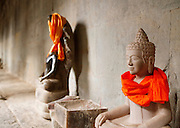 Buddhist statues adorned with colourful cloth in Angkor Wat at Angkor, Siem Reap Province, Cambodia
