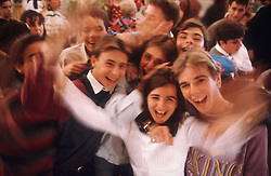 Group of young people at Spring Fair; Seville; laughing and waving,