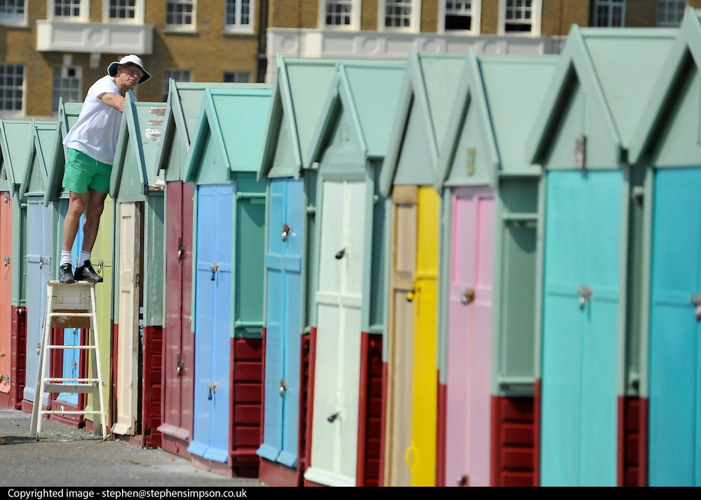 licensed to London News Pictures. BRIGHTON  UK. 21/04/11.A  man paints a beach hut on Hove seafront. People flock to Brighton Beach today (21 April 11) to catch the sunshine before the start of the Easter Bank Holiday in Britain. Temperatures are set to continue to rise over the weekend. Photo credit should read Stephen Simpson/LNP