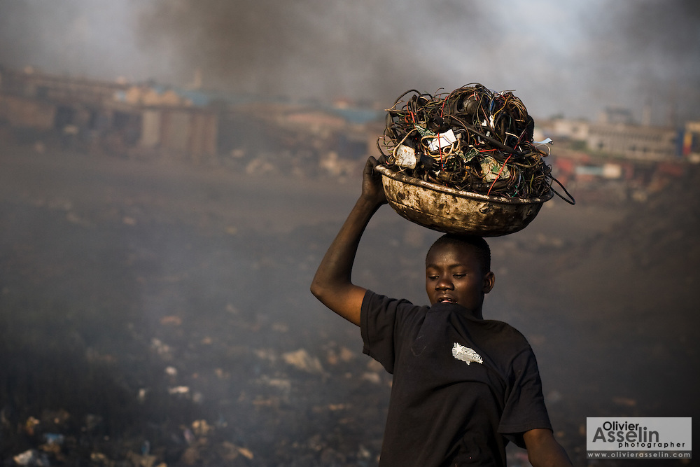 A boy carries a load of cables and wires from computers and other electronics as he prepares to set them on fire to recover copper near the Agbogboloshie market in Accra, Ghana on Thursday August 21, 2008.