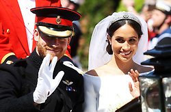 Prince Harry and Meghan Markle ride in an open-topped carriage through Windsor after their wedding in St George's Chapel.