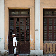 Man walking past building facade in Cienfuegos, Cuba