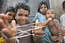 Prabhakar Bindhani, Age- 6 years, play Cats Cradle,a game with string or thread during the opening session of the Registration promotion and legal Aid session.<br /> CLAP runs many programmes in this area to promote community rights and provide legal support for individuals and communities especially slum communities such as this that have no land rights.   Programme: Community Awareness Programme on Birth Registration. Dobandhanagar Community, Cuttack City, INDIA