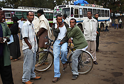Men wait to greet travelers at the main bus station in Bahir Dar, Ethiopia on May 28, 2007. Brokers often look for young girls traveling alone, promising them a good life with lots of money. Often they are trafficked to brothels in exchange for a mere $5. Workers from the Forum for Street Children, a local NGO, have teamed up with the local police to help curb this occurrence, educating brokers about childrens' rights and trying to intercept the girls before they meet the brokers.