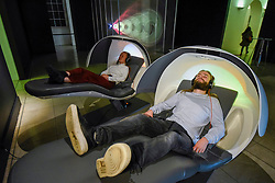 "© Licensed to London News Pictures. 29/10/2019. LONDON, UK. Staff members experience ""MetroNaps EnergyPods"".  Preview of ""24/7: A Wake-Up Call For Our Non-Stop World"", a new exhibition opening on 31 October at Somerset House.  The show examines our inability to switch off from our 24/7 culture.  Over 50 multi-disciplinary works explore the pressure to produce and consume information around the clock. taking visitors on a 24-hour cycle from dawn to dusk through interactive installations.  Photo credit: Stephen Chung/LNP"