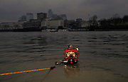 A Metropolitan Police diver surfaces beneath the murky waters of the River Thames in front of the tall buildings of the City of London, on 13th June 1993, in London, England. Blowing bubbles, he exhales through his oxygenated mask and looks through the Plexiglass to the viewer. The Underwater and Confined Space Search Team (UCSST), are part of the Marine Support Unit and based at Wapping. They also carry out searches in canals, ponds, lakes and reservoirs. It was set up as a full time unit in 1964. One of their most distressing jobs, however, is recovering bodies from the River. On average over 50 people lose their lives in the Thames each year and about 80% of these are by suicide (usually by jumping off one of the many bridges that cross the Thames). After a body is recovered from the River it is taken to the mortuary at Wapping Police Station for identification.