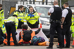 Enfield, UK. 15th September, 2021. A Metropolitan Police officer examines a glue container as Insulate Britain climate activists block a slip road from the M25 at Junction 25 as part of a campaign intended to push the UK government to make significant legislative change to start lowering emissions. The activists, who wrote to Prime Minister Boris Johnson on 13th August, are demanding that the government immediately promises both to fully fund and ensure the insulation of all social housing in Britain by 2025 and to produce within four months a legally binding national plan to fully fund and ensure the full low-energy and low-carbon whole-house retrofit, with no externalised costs, of all homes in Britain by 2030 as part of a just transition to full decarbonisation of all parts of society and the economy.