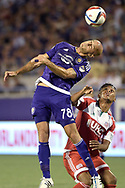 Orlando City defender Aurelien Collin (78) heads the ball over New England Revolution forward Juan Agudelo, right, during the first half of an MLS soccer game in Orlando, Fla., Friday, May 8, 2015. (AP Photo/Phelan M. Ebenhack)