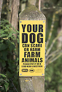 Yellow warning sign on post about danger of dogs worrying farm animals. Your dog can scare or harm farm animals please put it on a lead near livestock.