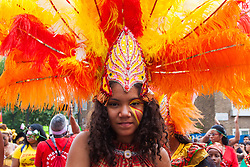 "London, August 24th 2014. A young woman's feathered headress makes for  a colourful display  as thousands of Londoners of all races and cultures attend Notting Hill Carnival's ""Family friendly"" day ahead of the main carnival on August Bank Holiday Monday."