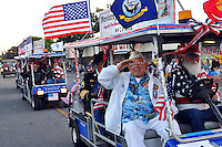 Service members riding with the Monterey Bay Veterans float salute the crowds at Saturday's 2013 Colmo del Rodeo Parade in Salinas.