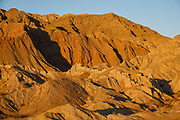 Sunset illuminates eroded land in Mecca Hills Wilderness. BLM dispersed campsite off Painted Canyon Road, Mecca, California, USA. Mecca Hills Wilderness is managed by BLM's Palm Springs-South Coast Field Office. The Mecca Hills are deeply-eroded sedimentary badlands north of the Salton Sea, bounded on the west by the San Andreas Fault. Several parallel faults split the region. The original sediments were primarily lake and Colorado River deposits, later covered with alluvium as the uplifting hills eroded.