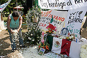 14 SEPTEMBER 2003 - CANCUN, QUINTANA ROO, MEXICO:  A Mexican woman spreads flowers at shrine, Sunday, dedicated to Lee Kyung-hae, a Korean farm activists who publicly committed suicide Wednesday in Cancun to protest World Trade Organization agricultural policies, where he died in a park in Cancun. Thousands of protestors opposed to the World Trade Organization and globalization have come to Cancun to protest the WTO meetings taking place in the hotel zone. Mexican police restricted most of the anti-globalization protestors to downtown Cancun, about five miles from the convention center.  PHOTO BY JACK KURTZ