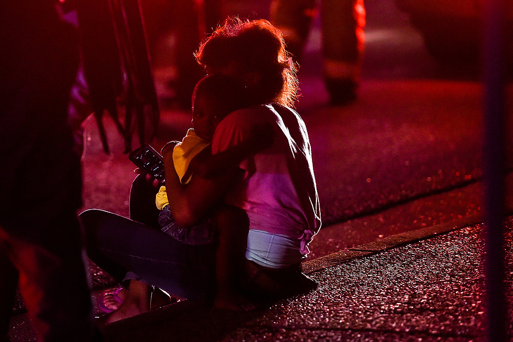 A child clings to his mother as she sits on the curb after a two-vehicle crash at the intersection of North College Street and Glenn Avenue in Auburn, Ala. left her car totaled and sent one person to the hospital on Saturday, May 9, 2015. <br /> Zach Bland Photo