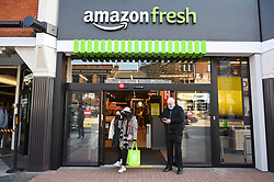 © Licensed to London News Pictures. 07/03/2021. London, UK. Customers exit the first AMAZON GO grocery store in the UK. The grocery store opened earlier this week and features contactless payment via the AMAZON app. Shoppers need to use app to shop inside the store and pick up groceries without stopping to pay. Photo credit: Ray Tang/LNP