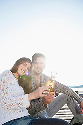 Young man woman sitting jetty drinking beer