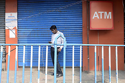 November 9, 2016 - Kolkata, West Bengal, India - Bank employe check his mobile in front of close bank. .Business effected all over India as Union Government announcements to one day bank and ATM shut down around the nation due to withdraw of Rs. 500 and Rs. 1000 bank notes nationwide. (Credit Image: © Saikat Paul/Pacific Press via ZUMA Wire)