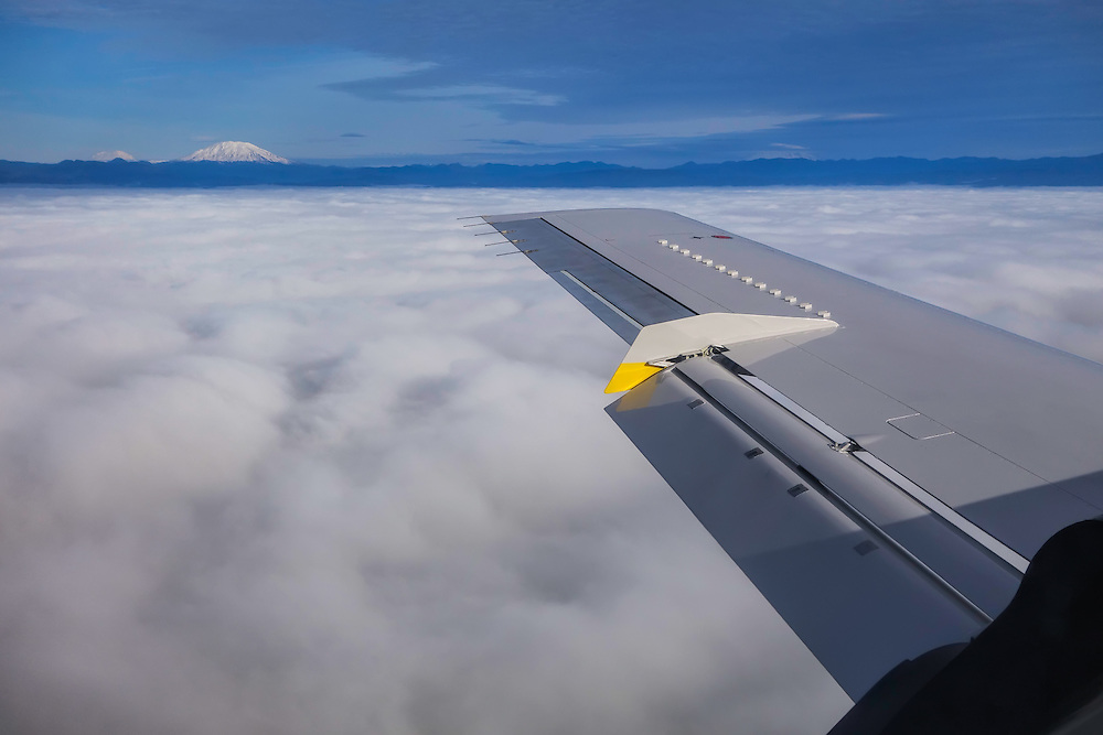 Airplane flying over the Portland, Oregon area on a cloudy winter day.  The Cascade Mountains in Washington, including Mt. St. Helens and Mt. Rainier, are visible to the north.