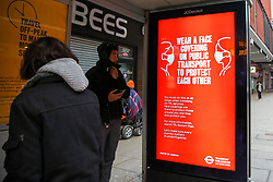 © Licensed to London News Pictures. 07/01/2021. London, UK. Commuters look at a Transport for London's 'Wear a face covering on public transport to protect each other' campaign poster at a bus stop in north London. Police have powers to fine people who are not wearing a coverings when travelling on public transport, including London buses. Lockdown measures are now in force across the UK, after Prime Minster Boris Johnson announced the new restrictions earlier this week asked everyone to 'stay at home' and only leave for the specific reasons, until mid-February. Photo credit: Dinendra Haria/LNP