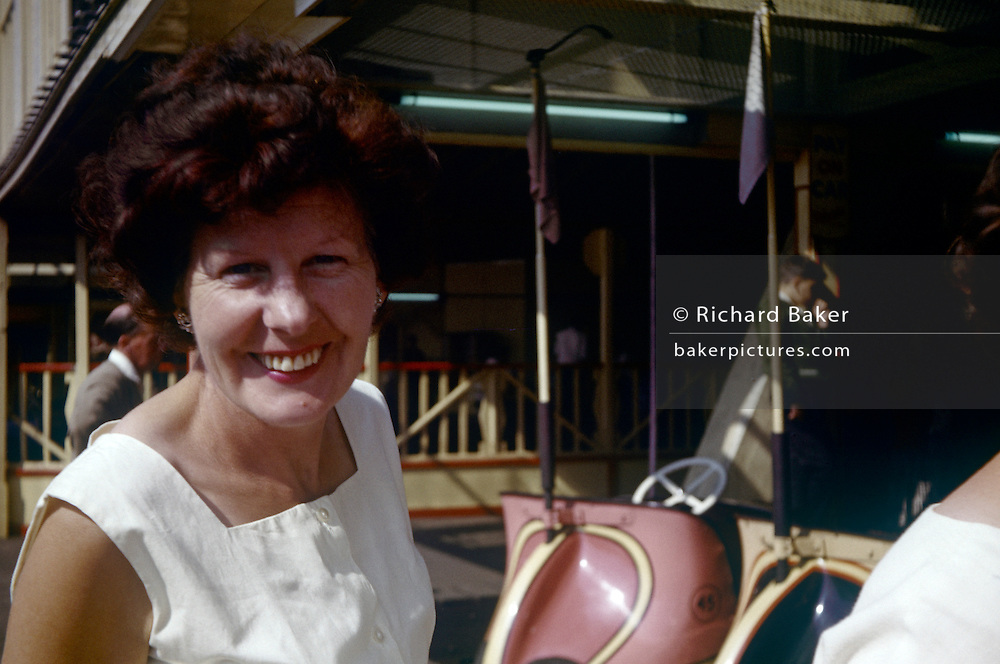 A lady smiles in a portrait near dodgem cars at the seaside during summer time in the early 1960s. The happy woman smiles to the film camera in a portrait on Southend Pier and recorded on a film camera by a relative, an amateur photographer in 1962. The picture shows us a memory of nostalgia in an era from the last century.