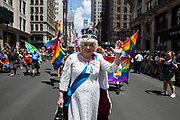 New York, NY - 30 June 2019. The New York City Heritage of Pride March filled Fifth Avenue for hours with participants from the LGBTQ community and it's supporters. A man costumed as Queen Elizabeth leads a group from the U.K.