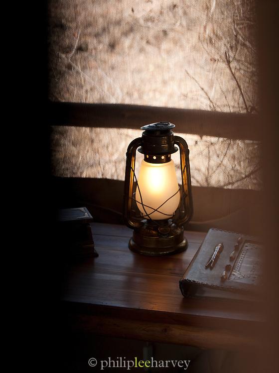 Hurrican lamp on the desk of a hut in an eco camp, Chyulu Hills region, Kenya