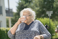 Senior woman on wheelchair drinking a glass of water, Bavaria, Germany