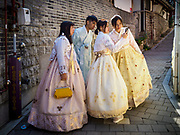 """SEOUL, SOUTH KOREA: Tourists wearing traditional Korean """"Hanbok"""" clothing, walk around and take selfies in the Bukchon Hanok village in Seoul. Hanok is the traditional style of construction in South Korea and Bukchon is one of the only remaining Hanok communities in Seoul. It is close to Gyeongbokgung Palace and popular with tourists.      PHOTO BY JACK KURTZ"""
