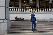 A homeless man lies on City seating as a businessmen smokes, on 14th September 2017, in the City of London, England.
