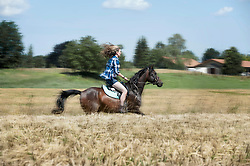 Young woman riding galloping horse in wheat field, Bavaria, Germany