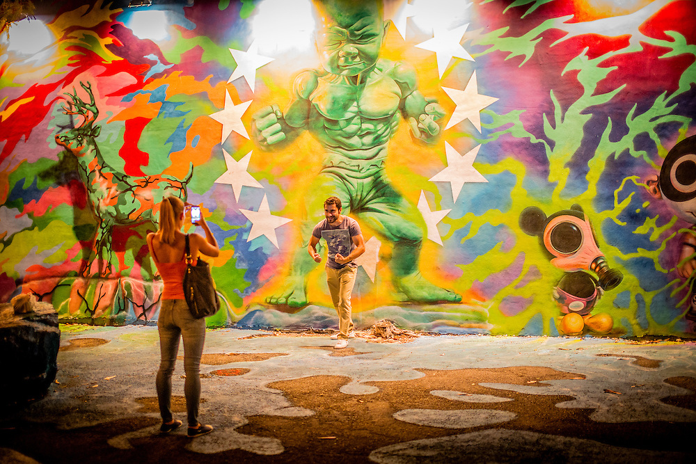 A visitor to Miami's Wynwood Walls strikes a pose with a Baby Hulk mural by Ron English
