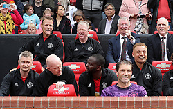 Manchester United Legends manager Sir Alex Ferguson (centre right) in the dugout during the legends match at Old Trafford, Manchester.