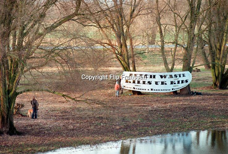 Nederland, Dodewaard, december 2000Actievoerders met spandoek bij het eerste kerntransport van Dodewaard naar Sellafield in Engeland. Een beveiliger van de GKN houdt met zijn hond een oogje in het zeil . Anti kernenergie, Milieu, Greenpeace .Foto: Flip Franssen