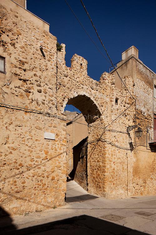 Naro, Italia - il 16 September 2012:  La Porta d'Oro (o Porta Vecchia) è l'unica rimasta delle sei porte che permettevano l'accesso alla città di Naro nel periodo medievale.a Naro, Italia, il 16 September 2012. La porta fu edificata insieme alle mura di cinta della città, che delimitavano un'area romboidale, nel 1263. Nel 1482 le mura furono restaurate ma nel XVIII secolo, venute meno le funzionalità difensive, furono man mano distrutte. La porta d'oro rappresenta uno dei pochi tratti della cinta muraria conservatisi pressoché intatti fino ai giorni nostri. Il suo nome deriva dalla ricchezza proveniente dai commerci degli ebrei che proprio vicino a tale porta avevano il loro ghetto e dalla gran quantità di frumento che, proveniente dalle campagne sottostanti, entrava in città attraverso tale porta.