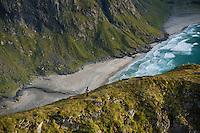 Female hiker overlooking Kvalvika beach from nearby mountain, Moskenesoy, Lofoten Islands, Norway
