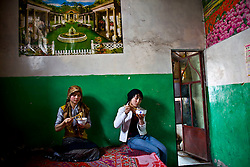 Mahire,19, left, eats lunch in her in-law's 500 years old house, which is scheduled to be demolished, in old city in Kashgar, China.