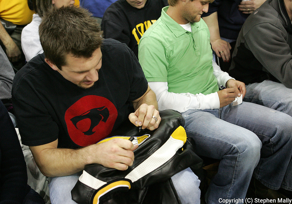 15 FEBRUARY 2007: Dallas Clark (TE - Indianapolis Colts) autographs a coat for a fan during Iowa's 66-58 win over Northwestern at Carver-Hawkeye Arena in Iowa City, Iowa on February 15, 2007.