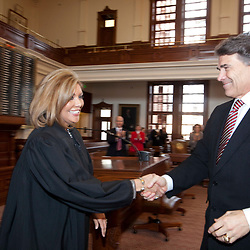 Texas Supreme Court Justice Eva Guzman, shakes hands with Governor Rick Perry after she is sworn into office on January 11, 2010 as the first Hispanic female Supreme Court Justice.  Guzman resigned effective June 11, 2021 a move which has prompted speculation she will run for Texas Attorney General against Ken Paxton.
