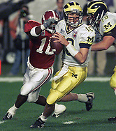 Michigan's quarterback Tom Brady searches for an open receiver during the first quarter of the 66th annual FedEx Orange Bowl game between the Michigan Wolverines and the Alabama Crimson Tide on January 1, 2000, at Pro Player Stadium in Miami Gardens, Florida. Michigan defeated Alabama 35–34 in an overtime battle.