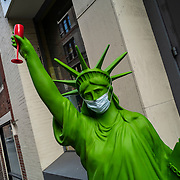 A wine holding Statue of Liberty wears a mask on the sidewalk as Manhattan streets remain sparse to both visitors and traffic during the Coronavirus (Covid-19) pandemic on Tuesday, January 19, 2021 in Manhattan, New York. (Alex Menendez via AP)