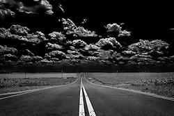 A long dark road in black and white stretches through a rural landscape in Wentzville, Missouri