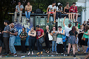 The 49th Notting Hill Carnival in West London. A celebration of West Indian / Caribbean culture and Europe's largest street party, festival and parade. Revellers come in their hundreds of thousands to have fun, dance, drink and let go in the brilliant atmosphere. People surrounding a nd sitting on a bus stop to get a better view along the parade route.