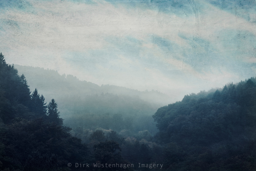 Forested hills and low hanging clouds and fog on a fall morning - photograph edited with texture overlays