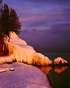 Winter sunset illuminating wave-splash icicles on shoreline rocks near the mouth of the Cascade River in Lake Superior, Cascade River State Park, Minnesota.