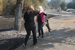 October 13, 2017 - Napa, California, U.S. - BARBARA CEFALU, right, rushes to hug neighbor MEL PREIMESBERGER, back to camera, upon seeing her on Friday morning outside their respective homes near Silverado Resort and Spa. Preimesberger's home was destroyed and she and her husband lost nearly everything, while Cefalu's home was relatively unscathed. (Credit Image: © J.L. Sousa, Register/Napa Valley Register via ZUMA Wire)