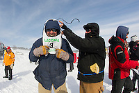 Keith Bryar gets some help putting on his bib by Peter Colbath prior to the start of the final Open Class race at the 86th annual Laconia World Championship Sled Dog Races on Sunday afternoon.  (Karen Bobotas/for the Laconia Daily Sun)