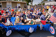 03 JULY 2021 - NORWALK, IOWA: Cub Scouts throw candy to the crowd during the 4th of July parade in Norwalk, Iowa. Last year's parade was cancelled because of the COVID-19 pandemic. Norwalk is an agricultural community south of Des Moines. In recent years, Norwalk has become a suburb of Des Moines.       PHOTO BY JACK KURTZ