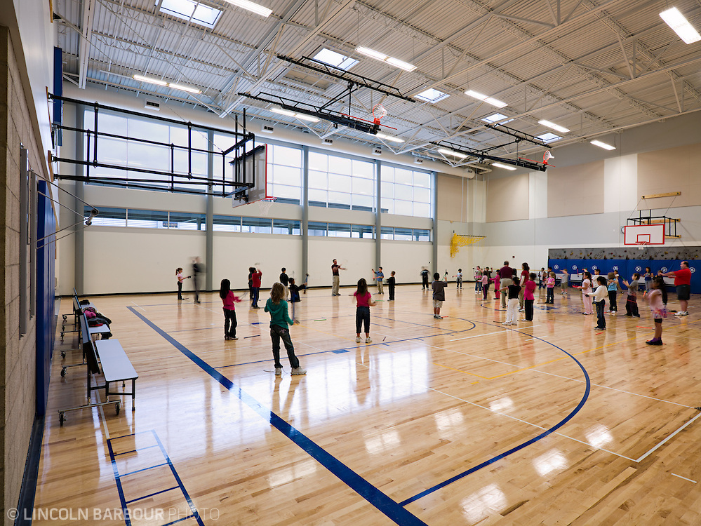 Grade school children in a gym being walked through some warm ups during physical education time.