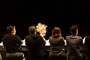 Brooklyn, NY - 11 December 2019. A performance of In Many Hands in BAM's Fishman Space, by Kate McIntosh in collaboration with Arantxa Martinez and Josh Rutter; sound design by John Avery; lighting design by Joëlle Reyms. The piece involves participants sitting at 3 long, narrow tables, with facilitators at each end, and either passing along objects—here a bunch of grass—or repeating hand movements in the manner set by a facilitator.